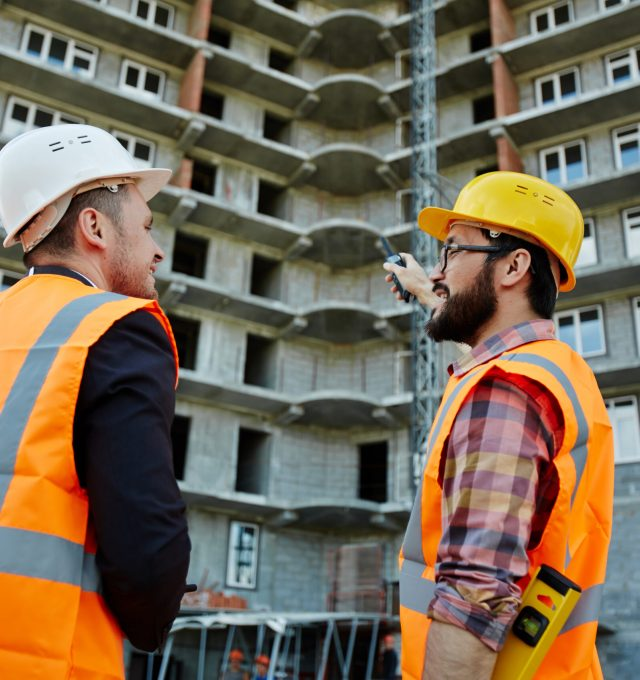 Back view of two workmen wearing reflective orange vests and hard hats standing on construction site, foreman explaining project details to inspector pointing at unfinished apartment building